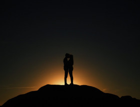 Silhouette of two people kissing on top of a rock, a sunrise behind them